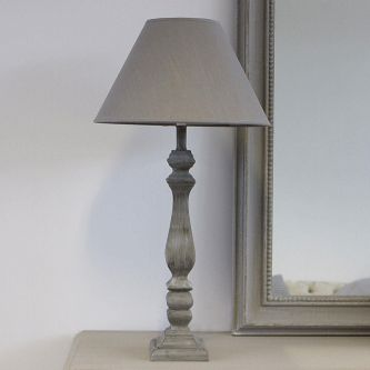 Table Lamp with Grey Linen Shade on a table next to a mirror.