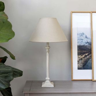 Table lamp with light linen shade on a table next to a picture frame.